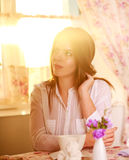 Girl at the table with a cup of coffee in morning sunlight Royalty Free Stock Photo