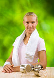 A girl at table with dumbbell Royalty Free Stock Images