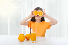 Girl at the table with oranges Royalty Free Stock Images