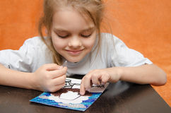 The girl at the table playing sand applique Stock Photography