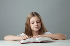 Girl at the table reading a book Stock Image