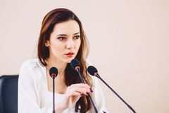 girl at the table speaks in microphones at conference hall stock photos