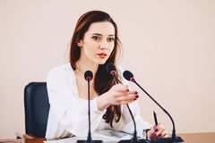 girl at the table speaks in microphones at conference hall royalty free stock photos