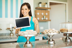 Girl with tablet in a cake shop. Portrait of a beautiful young woman holding a tablet computer and pointing at it while standing in a cake shop stock photography