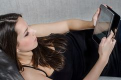 The girl with tablet. Communication with friends, young girl with tablet Stock Photography