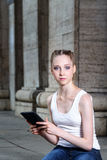 Girl with tablet computer. Girl in a white T-shirt with a tablet computer Stock Image
