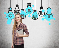 Girl with tablet and consult light bulbs. Blond woman with a tablet is standing near a concrete wall with light bulb sketches drawn on it and word consult. Blue stock photography