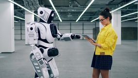 Girl with tablet controls a cyborg, typing on its panel. stock footage