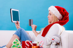 Girl with tablet credit card doing online shopping. Christmas time concept. Young woman teen girl with tablet pc laptop and credit card on sofa at home doing Royalty Free Stock Photos