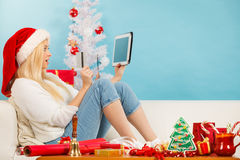 Girl with tablet credit card doing online shopping. Christmas time concept. Young woman teen girl with tablet pc laptop and credit card on sofa at home doing Royalty Free Stock Photography