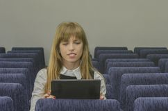 Girl with a tablet in an empty lecture hall Stock Images