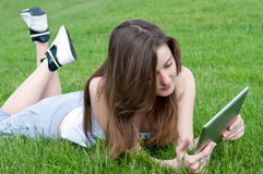 Girl with tablet on lawn. Stock Image