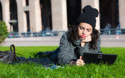 Girl with tablet, lying on green grass looking bored Royalty Free Stock Photography