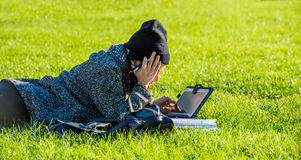 Girl with tablet, lying on green grass and writing on tablet bores from homework Stock Photos