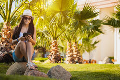 Girl with tablet in the palm garden Royalty Free Stock Photo