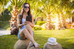 Girl with tablet in the palm garden Royalty Free Stock Photos