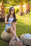 Girl with tablet in the palm garden Stock Image