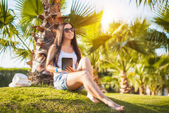 Girl with tablet in the palm garden Royalty Free Stock Photography