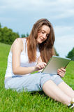 Girl with tablet in park on grass. Stock Photos