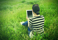 Girl with tablet in park on grass. Royalty Free Stock Images