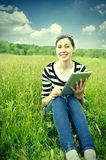 Girl with tablet in park on grass. Stock Image