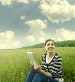 Girl with tablet in park on grass. Royalty Free Stock Image