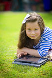 Girl with tablet in a park Stock Images