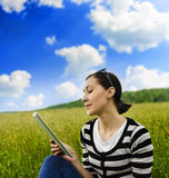 Girl with tablet pc on the grass. Royalty Free Stock Image
