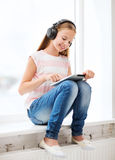 Girl with tablet pc and headphones at home Royalty Free Stock Photo