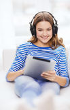 Girl with tablet pc and headphones at home Royalty Free Stock Images