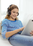 Girl with tablet pc and headphones at home Royalty Free Stock Photos