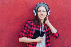 Girl with tablet pc. Portrait of happy hipster woman holding tablet computer and listening music in headphones. Girl using digital tablet outdoors. Technology Royalty Free Stock Photography