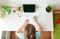 Girl with tablet pc writing to notebook at home Stock Photo