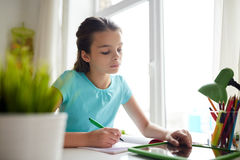 Girl with tablet pc writing to notebook at home Royalty Free Stock Photos