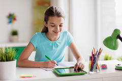 Girl with tablet pc writing to notebook at home Royalty Free Stock Images