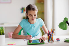 Girl with tablet pc writing to notebook at home Royalty Free Stock Photography