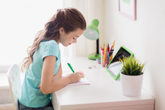 Girl with tablet pc writing to notebook at home Stock Images