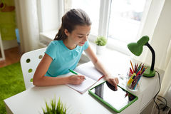 Girl with tablet pc writing to notebook at home Stock Image