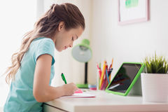 Girl with tablet pc writing to notebook at home. People, children, education and learning concept - happy girl with tablet pc computer writing to notebook at Royalty Free Stock Image