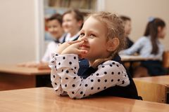 Girl with tablet raising hand in elementary school class royalty free stock photos