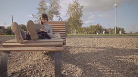 Girl with tablet sits on wooden deck chair on pebble beach in cool day. Young woman in glasses uses tablet while sitting on wooden deck chair on pebble beach in stock video footage
