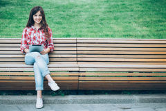Girl with tablet sitting on a park bench Stock Images