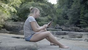 Girl with tablet sitting on a rock near a mountain stream. stock video footage