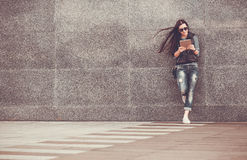 Girl with tablet is walking in the downtown Stock Photo