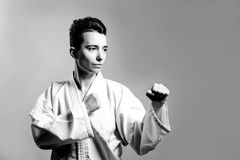 Girl, Taekwondo is martial Stoke hands in fists, focused, serious look in the Studio on gray isolated background royalty free stock photography