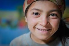 Girl in Tajikistan. Wakhan valley, Tajikistan - circa October 2011: Young girl with brown headcloth on her head smiles in Wakhan valley, Tajikistan. Documentary Stock Photos