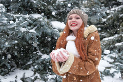Girl take a handful of snow in winter park at day. Fir trees with snow. Royalty Free Stock Photo