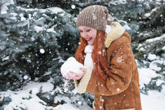 Girl take a handful of snow in winter park at day. Fir trees with snow. Stock Photos