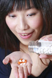 Girl take medicine. Asian girl pour pills on the hand. Simulated Royalty Free Stock Photo