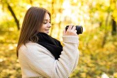 Girl take photo with camera in yellow autumn Royalty Free Stock Photos